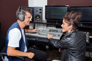 Happy young man and female professionals mixing audio in recordi