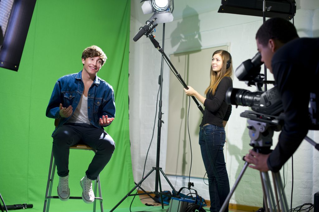 People filming a scene on a green screen.