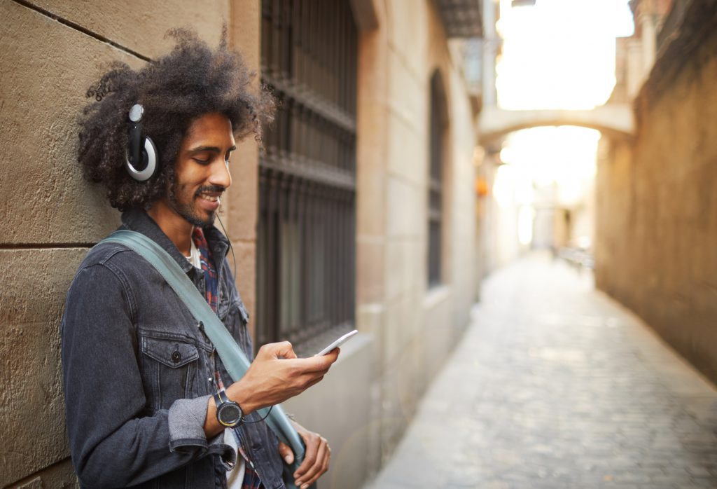 Man leaning against the wall with headphones listening to an app used for music distribution.